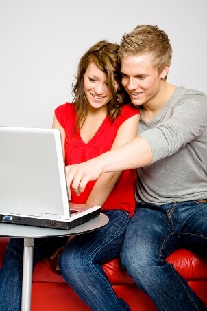 A young engaged couple learns about titanium wedding rings online before